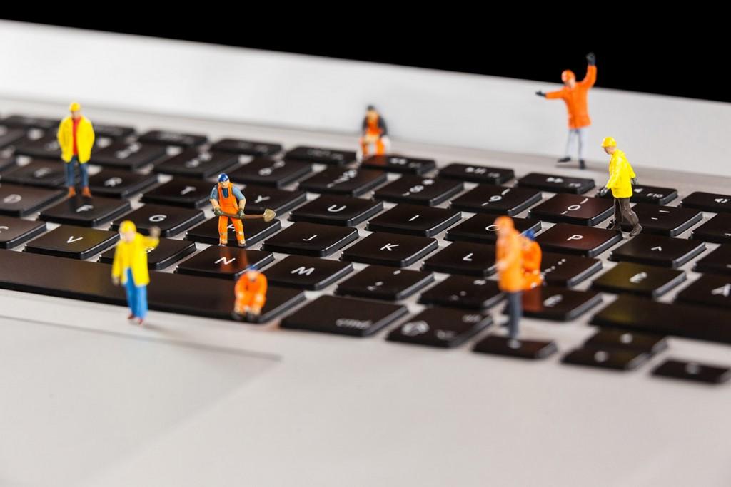 Conceptual image of miniature workmen repairing a laptop keyboard