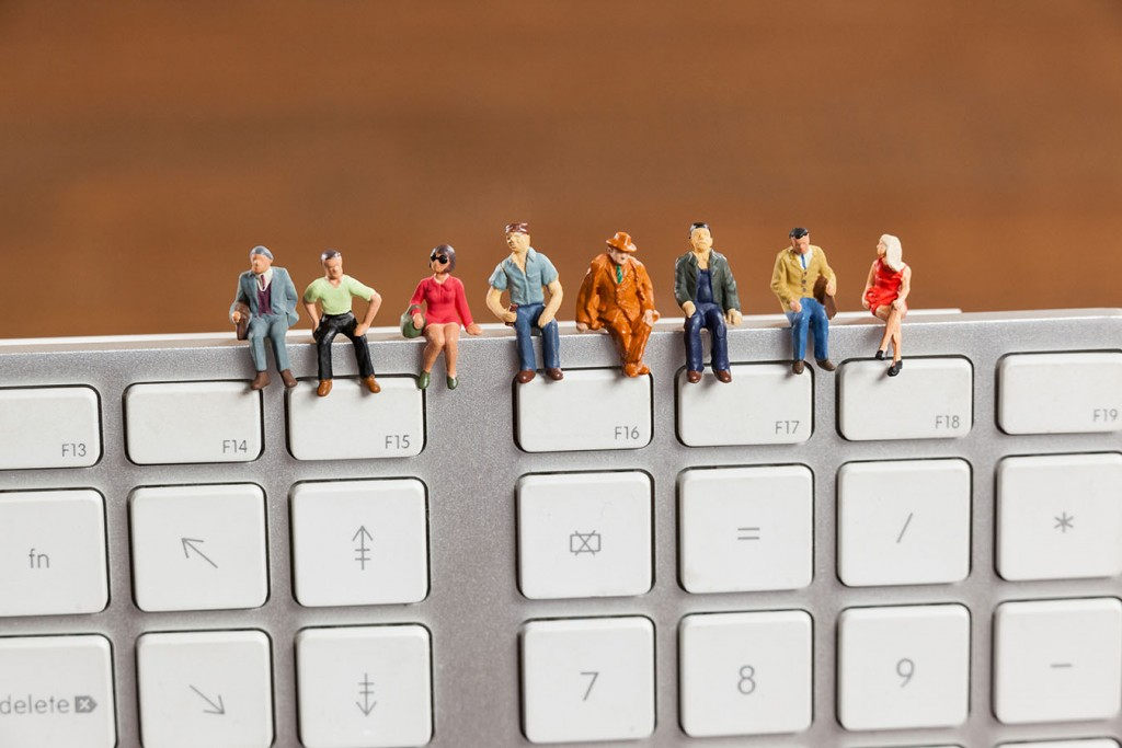 Conceptual image of miniature people sitting on top of keyboard
