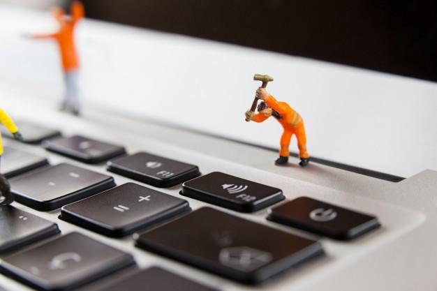 miniature-workmen-repairing-a-laptop-keyboard_1252-853